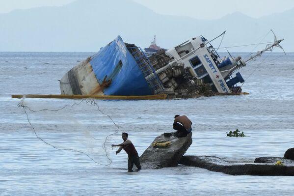 Rybář hází svou síť do moře poblíž napůl potopené lodi M/V Palawan Pearl. Loď se potopila poté, co se srazila s bagrem BKM 104 plujícím pod vlajkou Kypru v Manilském zálivu ve Filipínách. Čtvrtek 8. července. - Sputnik Česká republika