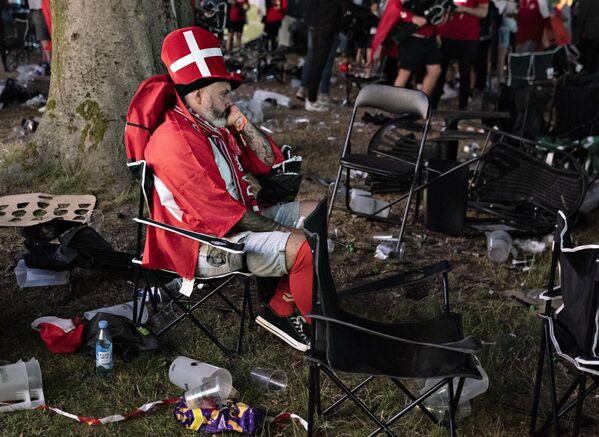 Dánský fotbalový fanoušek sedí v parku v Aalborgu poté, co Dánsko dne 7. července prohrálo 2:1 s Anglií v semifinále fotbalového zápasu UEFA Euro 2020. - Sputnik Česká republika