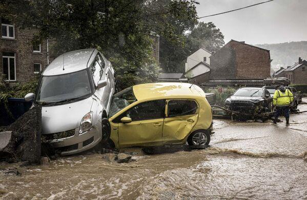 Snímek z belgické provincie Liege, na kterém muž prochází kolem rozbitých aut. Ve středu Belgii zasáhly silné deště, které napáchaly škody. - Sputnik Česká republika