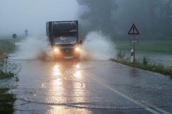 Dodávka jede zaplavenou silnicí nedaleko německého Kolína nad Rýnem, 15. července 2021. - Sputnik Česká republika