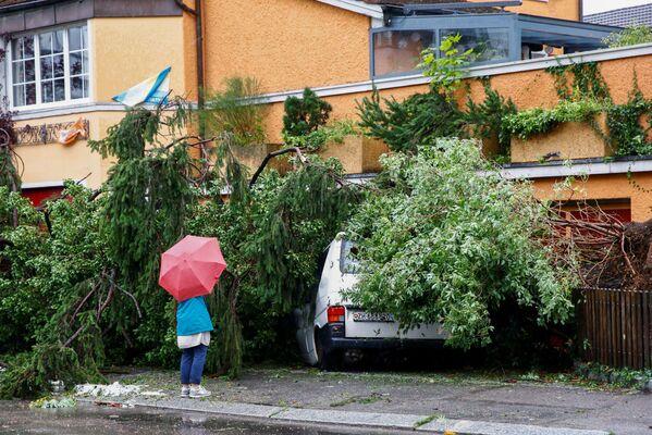 Žena stojí vedle dodávky zavalené spadlým stromem ve švýcarském Curychu, 13. července 2021. - Sputnik Česká republika