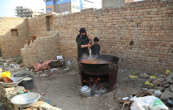 Lidé vaří jídlo v dočasném táboře pro postižené během vojenských střetů v Afghánistánu. - Sputnik Česká republika
