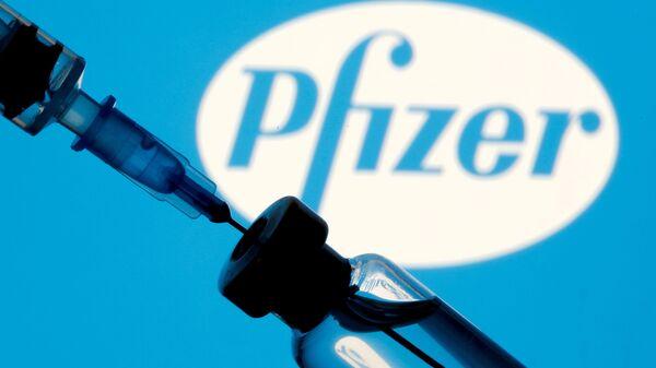 Шприц с ампулой на фоне логотипа Pfizer - Sputnik Česká republika