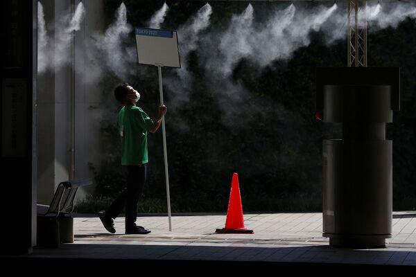 Волонтер под охлаждающим распылителем в Токио  - Sputnik Česká republika