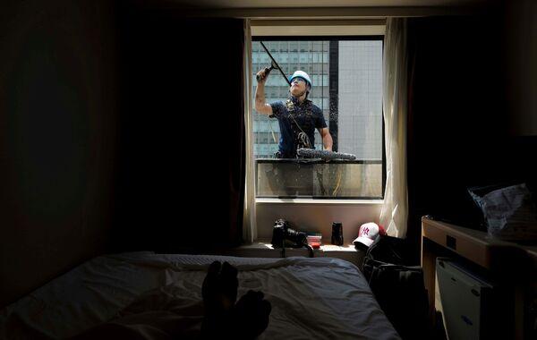 Fotograf v karanténě zachycuje pracovníka, který čistí hotelové okno v Tokiu - Sputnik Česká republika