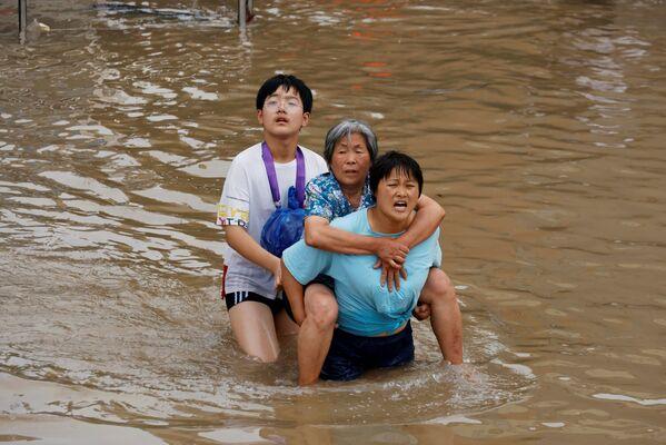 Žena pomáhá seniorce přejít zaplavenou ulici ve městě Čeng-čou. - Sputnik Česká republika
