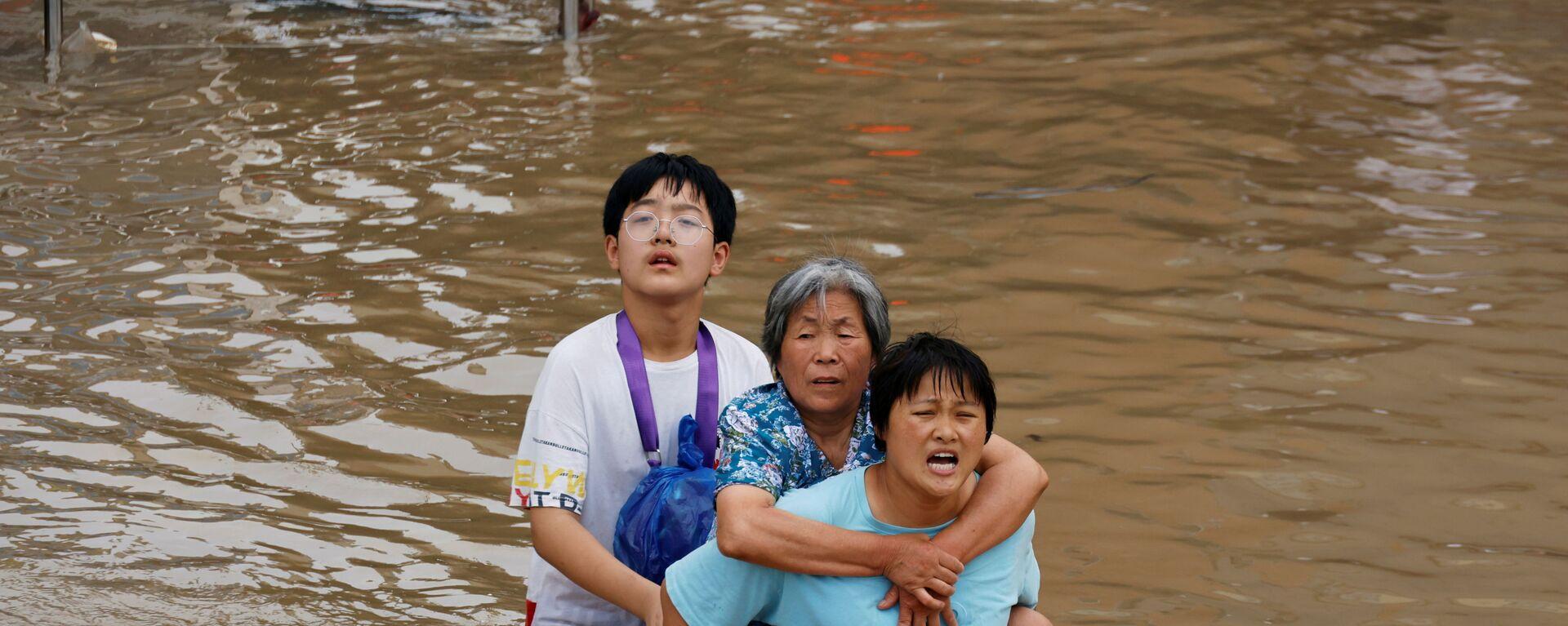 Женщина несет пожилую женщину  через паводковые воды после проливного дождя в Чжэнчжоу, провинция Хэнань, Китай - Sputnik Česká republika, 1920, 26.07.2021