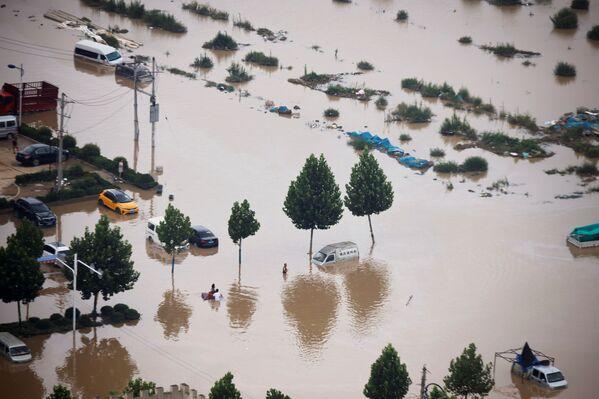 Auta na zaplavených ulicích ve městě Čeng-čou. - Sputnik Česká republika