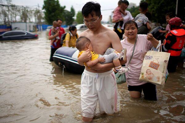 Muž drží miminko v náručí uprostřed zaplavené ulice ve městě Čeng-čou. - Sputnik Česká republika