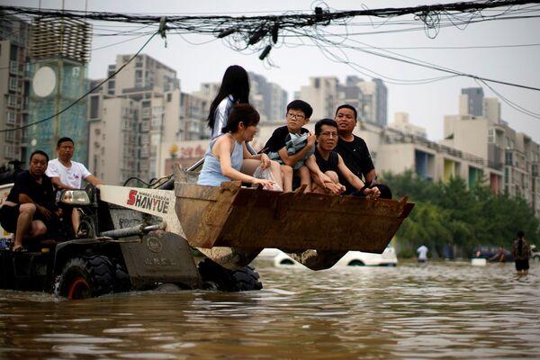 Lidé na zaplavené ulici ve městě Čeng-čou. - Sputnik Česká republika