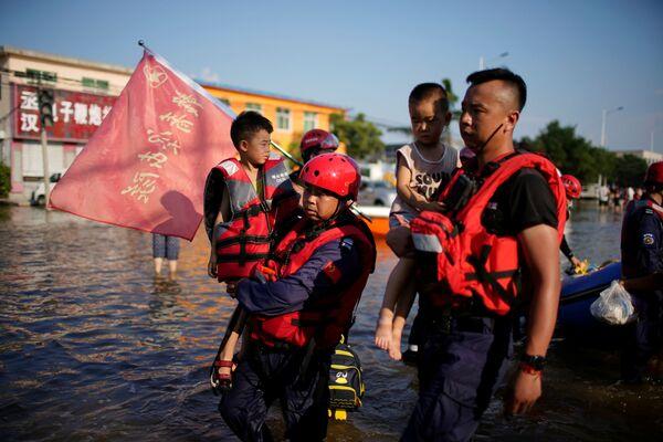 Záchranáři drží děti v náruči během evakuace ve městě Sin-siang. - Sputnik Česká republika