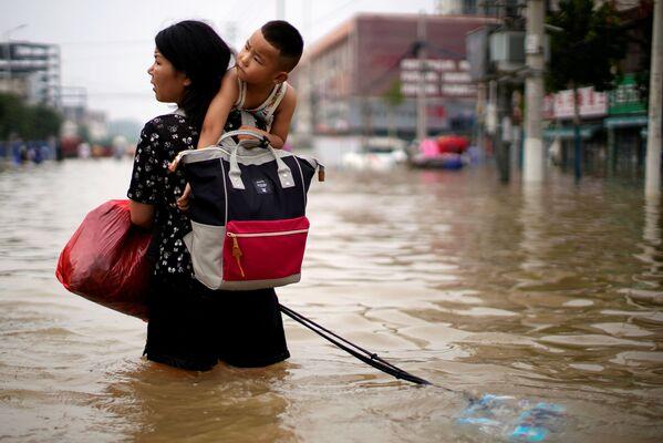 Žena se svým dítětem uprostřed zaplavené ulice ve městě Čeng-čou. - Sputnik Česká republika