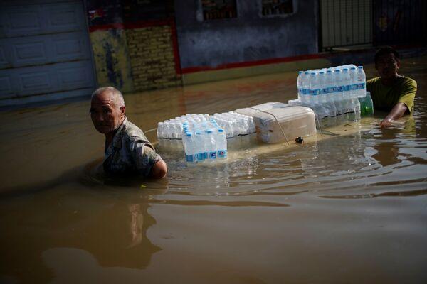 Dva muži s lahvemi vody uprostřed zaplavené ulice v provincii Che-nan. - Sputnik Česká republika