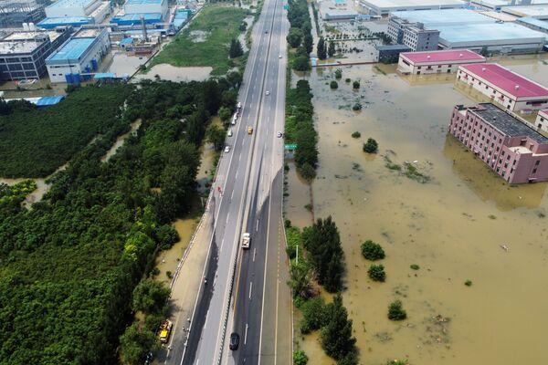 Snímek zaplavené průmyslové budovy poblíž hlavní silnice ve městě Sin-siang. - Sputnik Česká republika