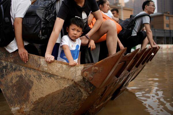 Lidé se přepravují přes ulici pomocí nakladače ve městě Čeng-čou. - Sputnik Česká republika