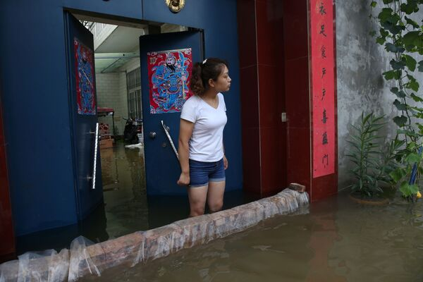 Obyvatelka vesnice ve svém zaplaveném domě v provincii Che-nan. - Sputnik Česká republika