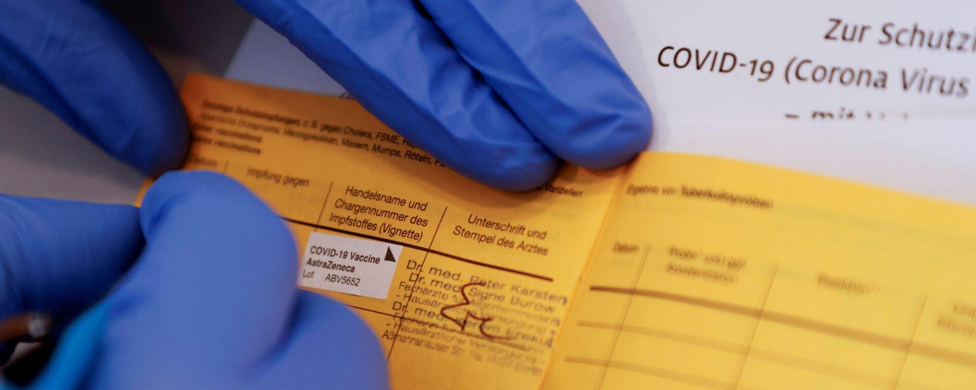 Lékař vyplní certifikát o očkování pacienta, po obdržení dávky vakcíny AstraZeneca - Sputnik Česká republika, 1920, 27.07.2021