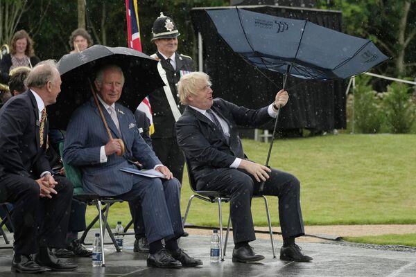 Britský princ Charles a premiér Boris Johnson se ukrývají před deštěm při otevření památníku britské policie v Národním památkovém ústavu v Alrewasu v Anglii. - Sputnik Česká republika
