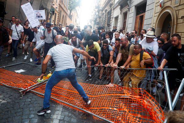 Demonstranti odstraňují policejní bariéru během demonstrace proti plánu Green Pass v Římě, Itálie. - Sputnik Česká republika