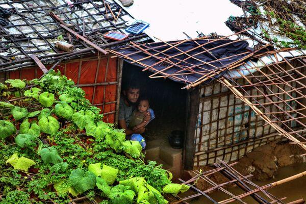Muž s dítětem v zatopeném  úkrytu v rohinském uprchlickém táboru Kutupalong v Bangladéši po silných deštích.  - Sputnik Česká republika