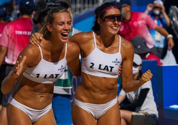 Tīna Graudiņa a Anastasia Kravčenko z Lotyšska slaví vítězství v osmifinálovém zápase ženského plážového volejbalu proti ruským sportovcům na XXXII. letních olympijských hrách v Tokiu - Sputnik Česká republika