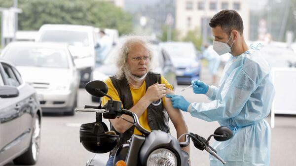 Zdravotnický pracovník aplikuje dávku vakcíny proti koronaviru v centru pro očkování v Berlíně - Sputnik Česká republika
