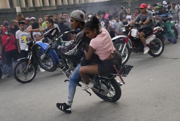 Motocyklista jede se spolujezdkyní během výstavy v oblasti El Valle ve venezuelském Caracasu - Sputnik Česká republika