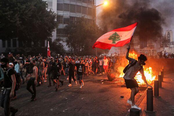Протестующий с ливанским флагом во время столкновенийв Бейруте - Sputnik Česká republika