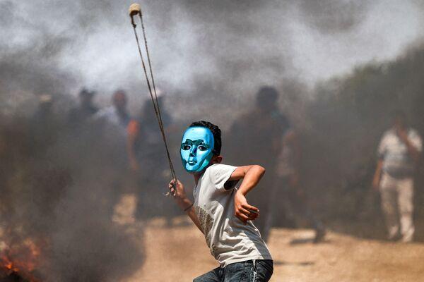 Палестинский ребенок в маске бросает камни во время столкновений с израильскими войсками в деревне Бейта на севере оккупированного Западного берега - Sputnik Česká republika