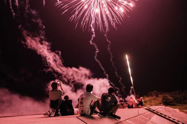 Люди запускают фейерверки на дамбе, реконструированной после цунами в 2011 году, в Минамисоме, префектура Фукусима, Япония - Sputnik Česká republika