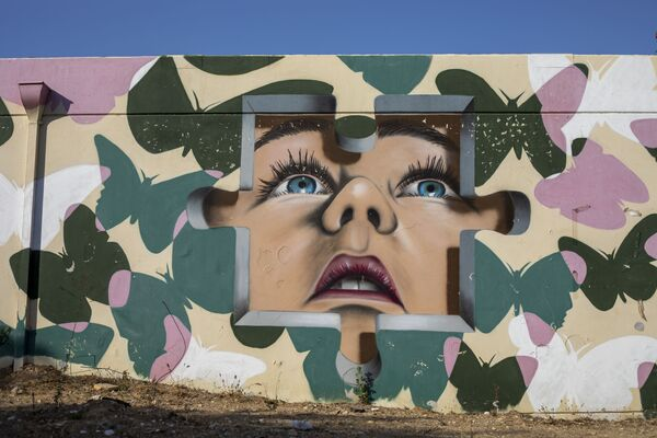 Betonový protiletecký kryt vyzdobený graffiti v izraelském městě Sderot poblíž hranice s Pásmem Gazy. - Sputnik Česká republika