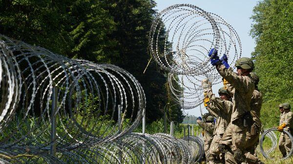 Солдаты литовской армии устанавливают забор из колючей проволоки на границе с Белоруссией в городе Друскининкай  - Sputnik Česká republika