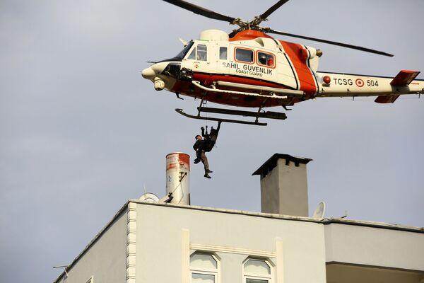Vrtulník pobřežní služby zachraňuje muže, který se dostal na střechu budovy během povodní ve městě Bozkurt. - Sputnik Česká republika
