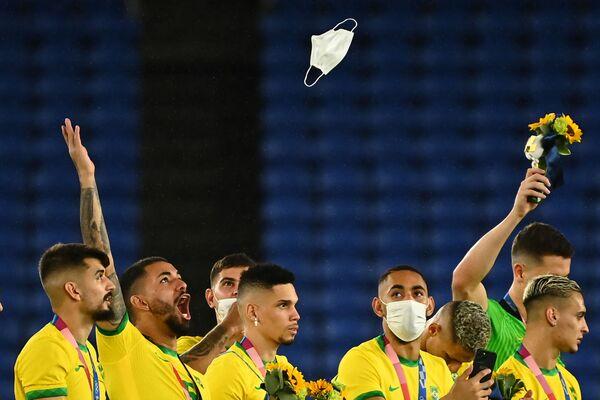 Zlatý brazilský medailista Douglas Luiz slaví na stupních vítězů při odevzdávání medailí fotbalového turnaje mužů v Tokiu. - Sputnik Česká republika
