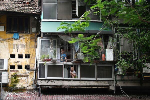 Děti se dívají z oken svého domova v Hanoji 11. srpna 2021 poté, co vláda vyhlásila dvoutýdenní lockdown, aby zabránila dalšímu šíření koronaviru. - Sputnik Česká republika