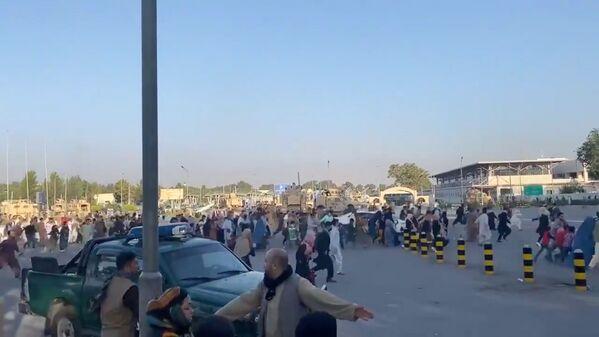 Skupina lidí běží k terminálu letiště v Kábulu poté, co hnutí Tálibán* převzalo kontrolu nad prezidentským palácem v Kábulu, 16. srpna 2021. - Sputnik Česká republika