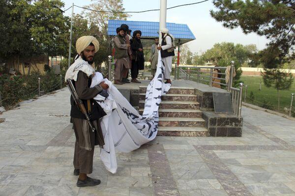 Členové hnutí Tálibán* vztyčují svoji vlajku ve městě Ghazní na jihovýchodě Afghánistánu, 15. srpna 2021. - Sputnik Česká republika
