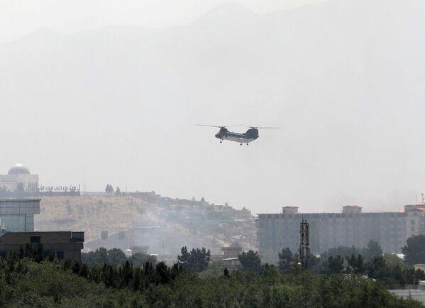 Vojenská transportní helikoptéra CH-46 Sea Hnight letící nad Kábulem 15. srpna 2021. - Sputnik Česká republika