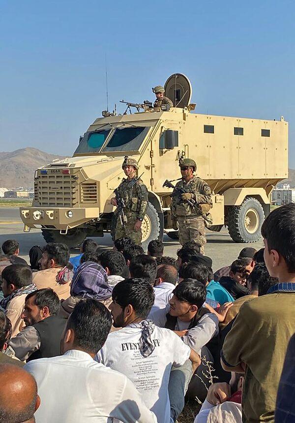 Američtí vojáci střeží letiště v Kábulu na pozadí tlačícího se davu. - Sputnik Česká republika