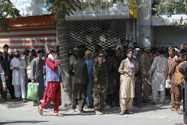 Afghánci hodiny čekají v dlouhých frontách před bankou v Kábulu, aby si mohli vybrat peníze. - Sputnik Česká republika