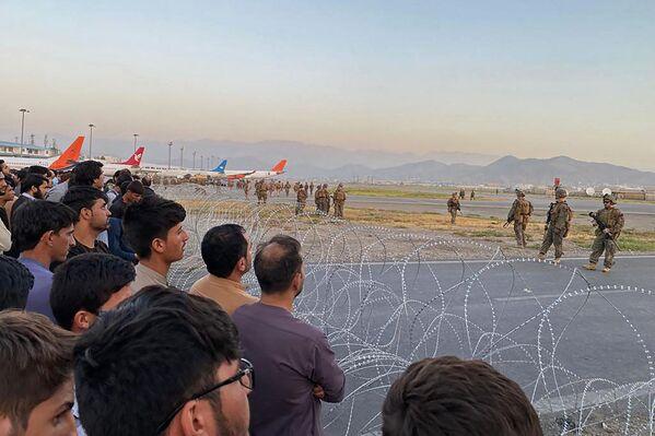 Američtí vojáci střeží letiště v Kábulu, zatímco Afghánci stojí za plotem. - Sputnik Česká republika