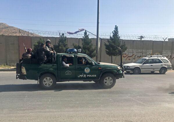 Členové Tálibánu* projíždí na policejním voze v Kábulu, 16. srpna 2021. - Sputnik Česká republika