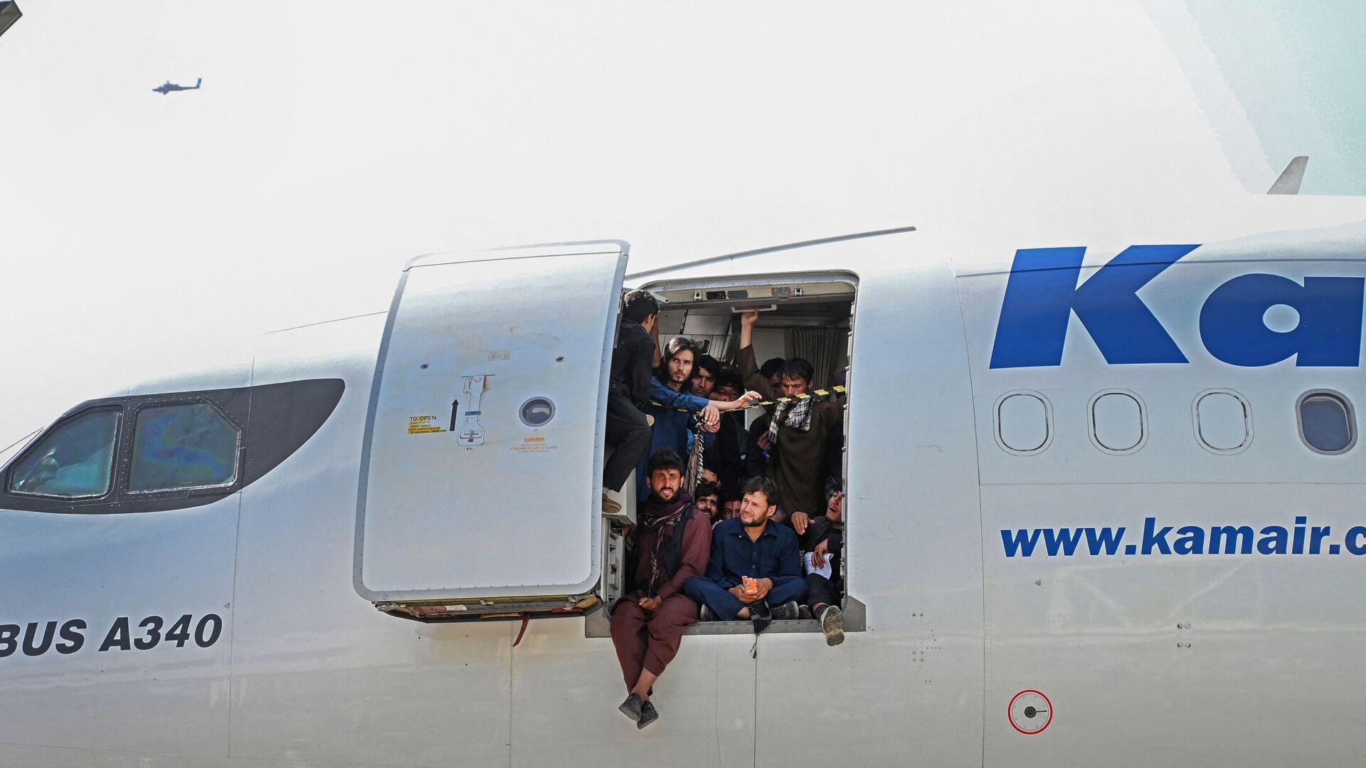 Afghánci ve dveřích letounu na letišti v Kábulu - Sputnik Česká republika, 1920, 12.09.2021