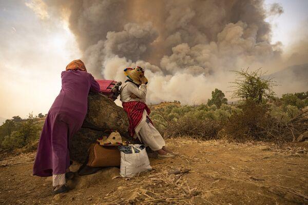 Marocké ženy se svými věcmi na pozadí dýmu z požárů, které 15. srpna 2021 zasáhly lesní oblast na severu Maroka. - Sputnik Česká republika