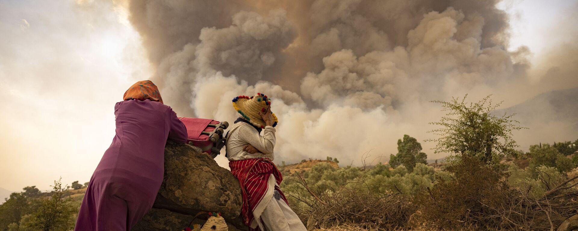 Женщины с вещами на дороге во время лесных пожаров в районе Шефшауэн на севере Марокко - Sputnik Česká republika, 1920, 17.08.2021