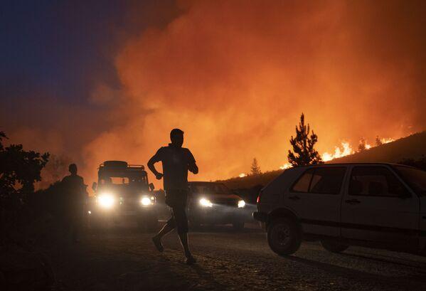 Snímek ukazuje lidi běžící před požárem, který zničil asi 200 hektarů lesa v oblasti Chafchaouen v severním Maroku, 15. srpna 2021. - Sputnik Česká republika