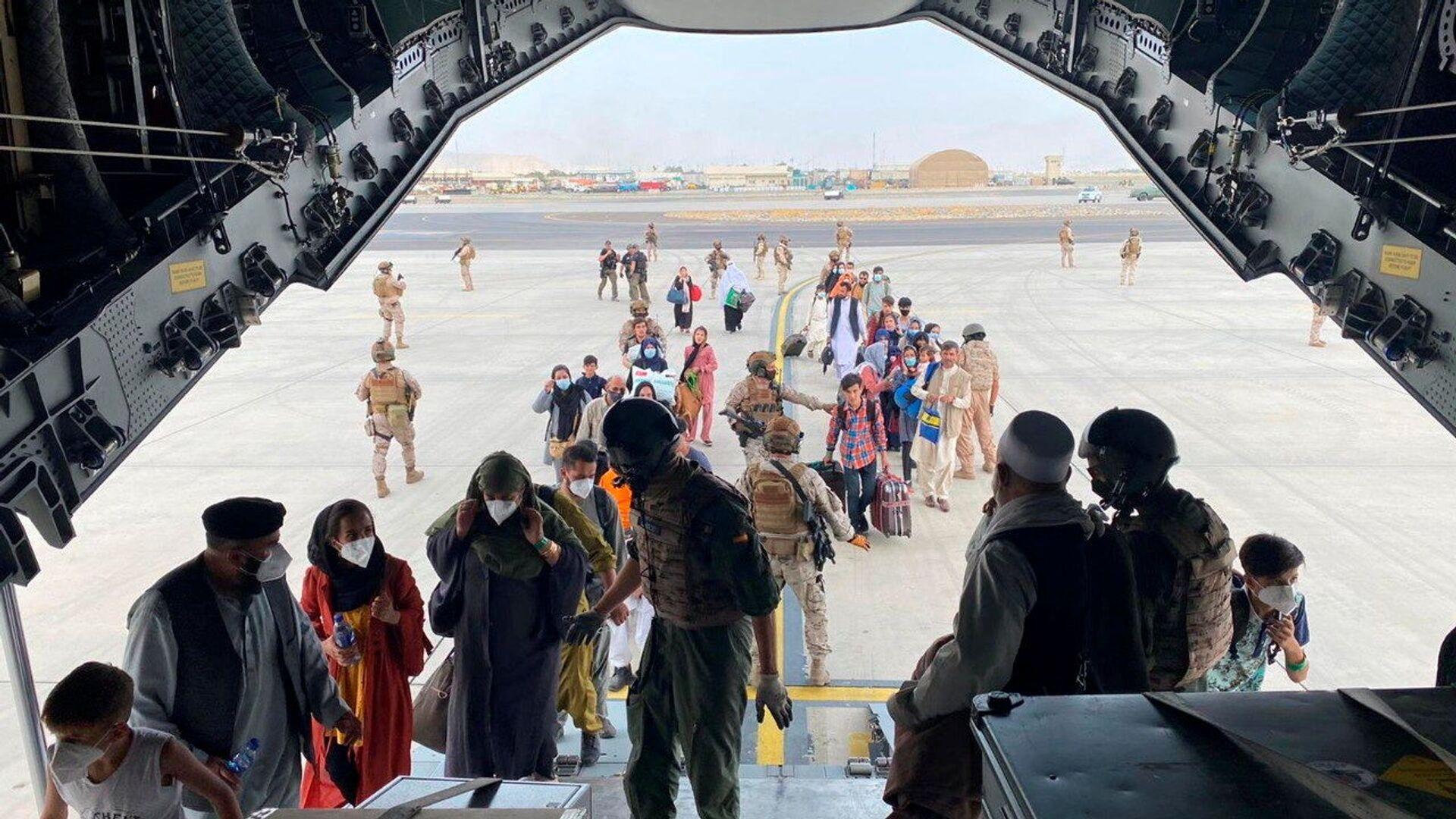 Španělští občané a Afghánci nastoupí do vojenského letadla v rámci evakuace na mezinárodním letišti v Kábulu - Sputnik Česká republika, 1920, 22.08.2021