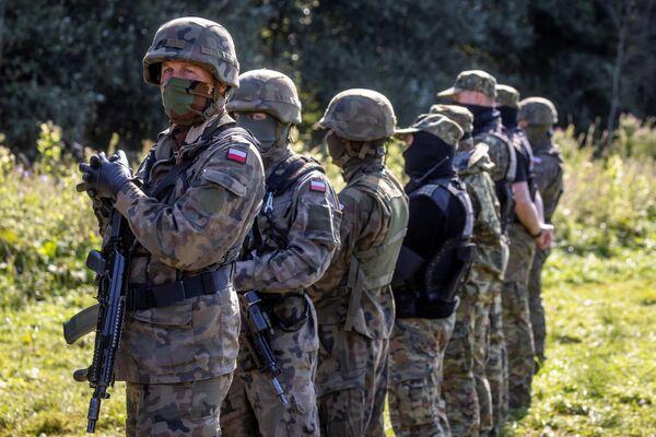Ozbrojení polští pohraničníci v improvizovaném táboře pro migranty na hranici Běloruska a Polska - Sputnik Česká republika