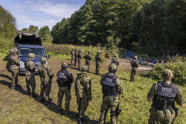 Polští a běloruští pohraničníci v improvizovaném táboře pro migranty na hranici Běloruska a Polska - Sputnik Česká republika