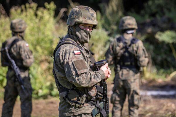Ozbrojená polská pohraniční stráž před skupinou migrantů v provizorním táboře na hranici Běloruska a Polska - Sputnik Česká republika